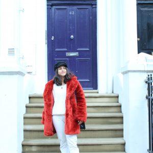 Red faux fur coat white jeans outside bright blue dor