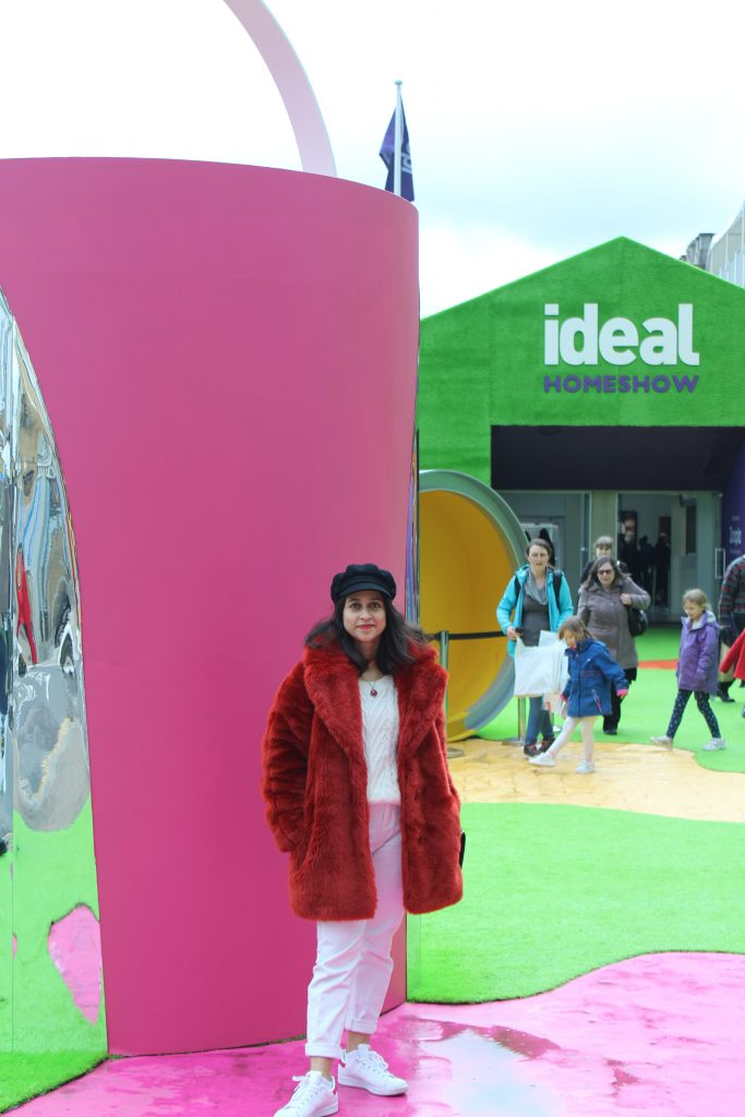 Red faux fur coat and white jeans standing outside pink and green backdrop of the Ideal Home Show