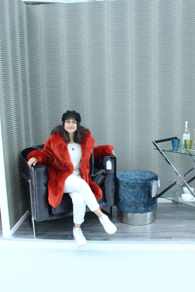 Red faux fur coat white jeans sofa ideal home show